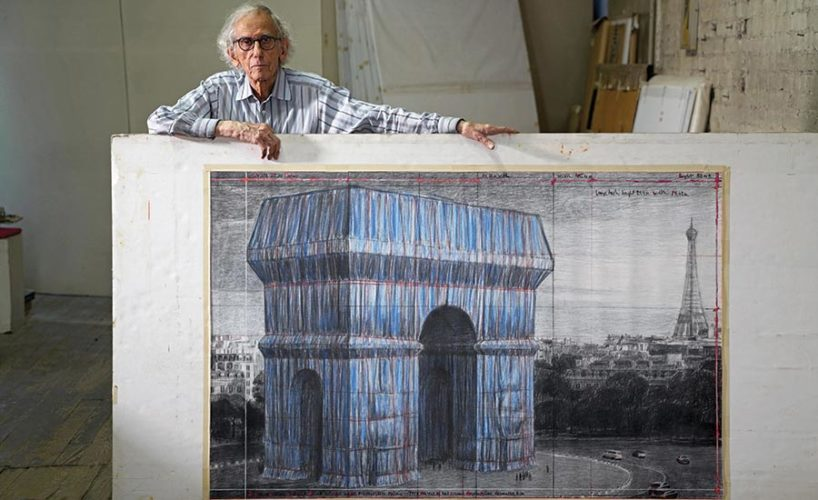 Christo in his New York studio in 2019, with a preparatory drawing for the project.
