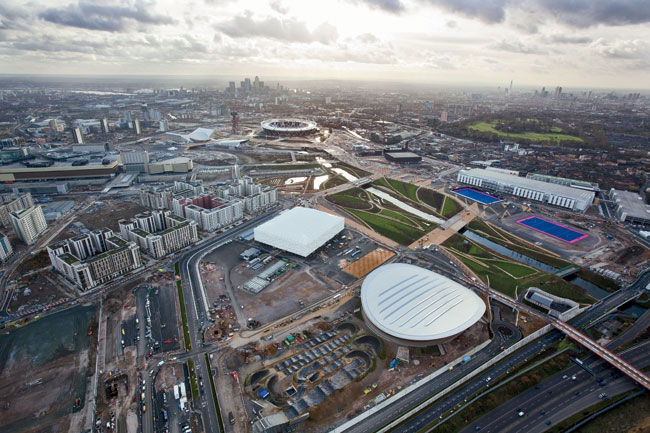 Clockwise, from top: The Olympic Stadium, Velodrome, Basketball Arena, Athletes' Village, and Aquatics Centre are each planned for long-term use and adaptation.