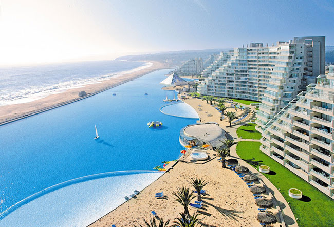 Largest swimming pool, 66 million gallons. Stretching 1,000 meters along Chile's Pacific coast, the Crystal Lagoon pool is flanked by the stepped towers of the San Alfonso del Mar resort. Completed in