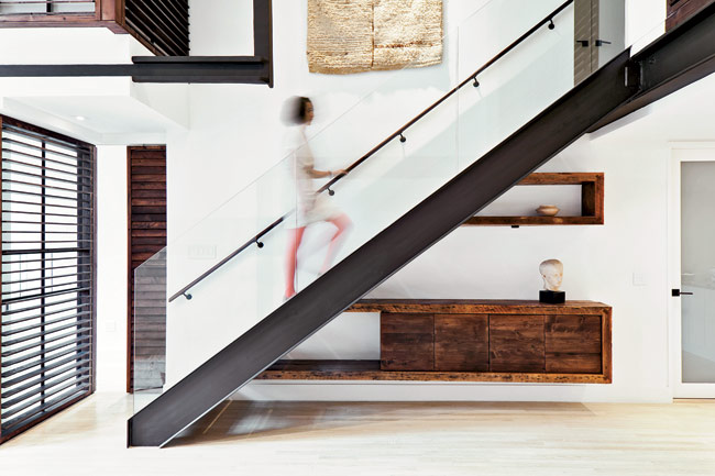 The repositioned stair comprises a steel stringer, enriched with reclaimed-wood treads and a transparent glass balustrade. Operable wood shutters, backed by glass panels that operate as dividers,