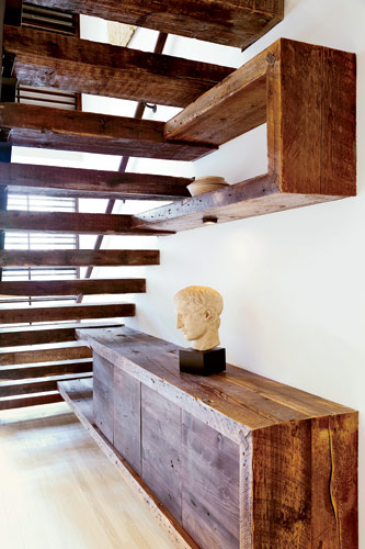 In keeping with her material scheme, Reddy designed a credenza and wall shelf to align with the stairs. Made out of the same reclaimed wood, these functional elements appear to float from the treads a