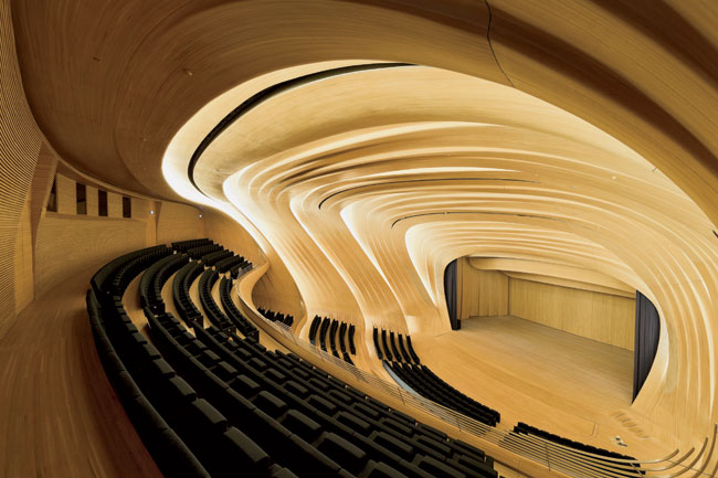Backlighting emphasizes the dynamism of the 1,000-seat auditorium's pleated oak paneling and underscores the contrast between the materials here and those used in the rest of the building.