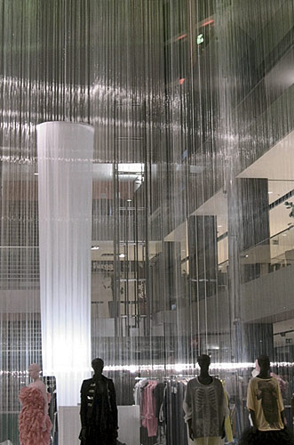 The architects spun a gossamer cocoon for a temporary fashion showroom in a Barcelona shopping center atrium, using 3,500 filaments of nylon fishing line that fell like a fine curtain of rain from the