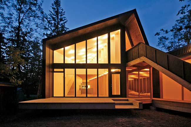 A family of four wanted to build a year-round retreat along the western shore of Lake Winnipeg, about an hour north of the city. In response, the firm designed an L-shaped house with outdoor living sp