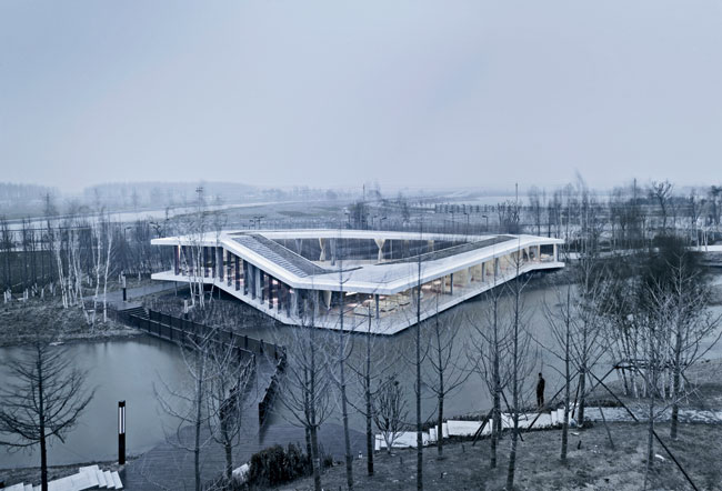 TAO took its design cues for this 5,380-square-foot building in Yancheng, 200 miles north of Shanghai, from the riverside site. The steel-framed, glass-walled building hovers above the ground, running