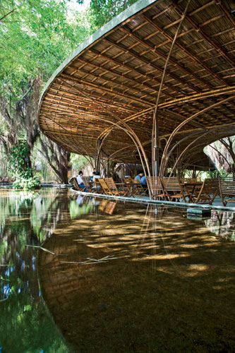 A pair of concentric crescents surrounded by a reflecting pool and nestled one within the other, this caf' in Binh Duong province places customers in a man-made landscape that helps connect interior a
