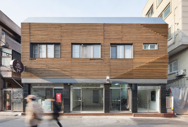 This residential project with street-front commercial spaces takes advantage of a grandfather clause that exempts existing buildings from having to provide parking. JOHO convinced the client to renova