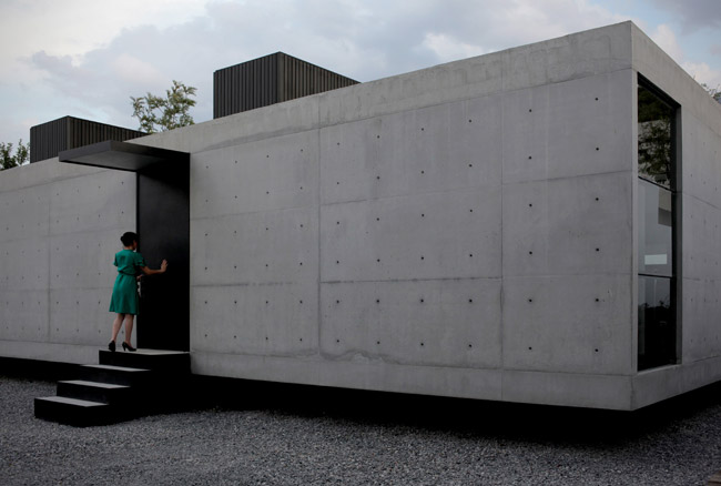 This private residence wears its rough material palette on its sleeve. Inside and out, the reinforced concrete walls and floors of the low box are left exposed and unadorned, punctuated by simple deta