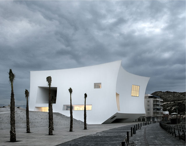 For a town on Spain's Mediterranean coast, the architects created a compact volume to minimize its occupation of the waterfront, and to create a point of reference in the landscape. The concave walls,