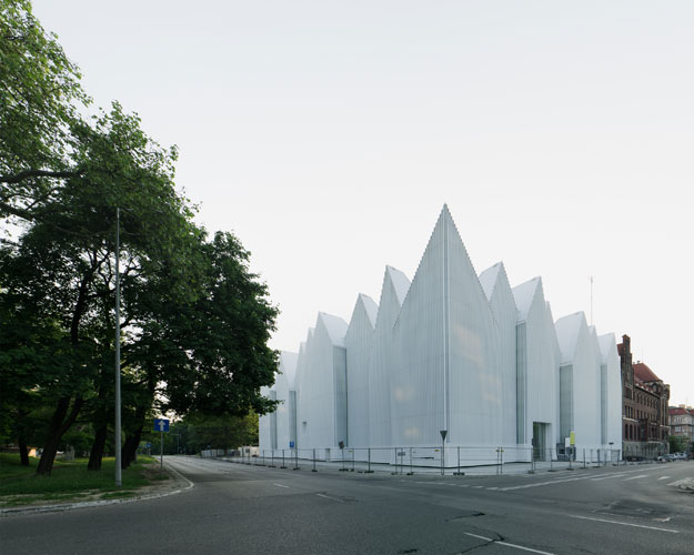 Occupying the site of a concert hall destroyed during World War II in this northwestern Polish city, the building's translucent glass form 'appears as a white mass in the daytime,' says Alberto Veiga,