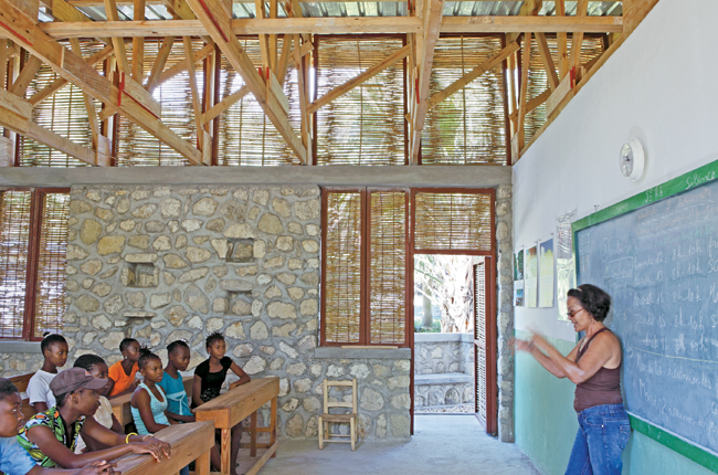 Openings covered with locally fabricated bamboo screens help ventilate the two-classroom building. Stones used for the foundation walls and entrance facade were collected from a nearby riverbed.