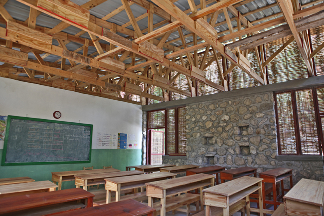 Openings covered with locally fabricated bamboo screens help ventilate the two-classroom building.
