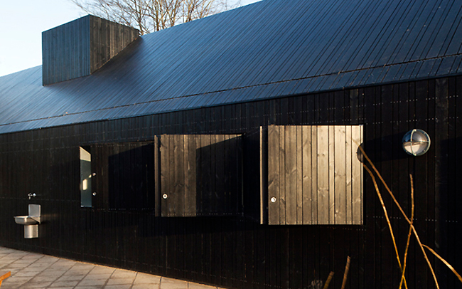 Black from charring, the wood cladding is mounted on the exterior of the existing building in an alternating pattern of three plank widths. It is heat modified to strengthen the wood.