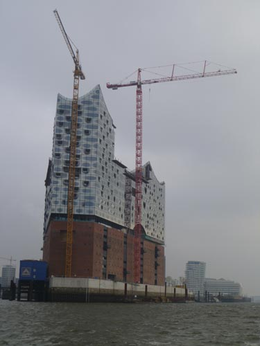 The Elbphilharmonie Concert Hall features a former cocoa warehouse crowned with a curved glass structure. The project has been plagued with cost overruns and construction difficulties; the estimated c