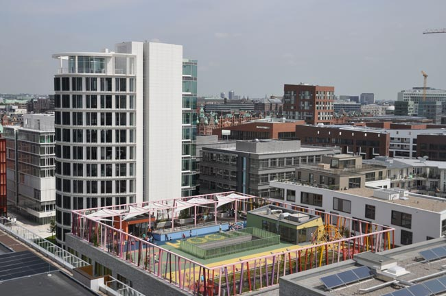 Katharinenschule school, designed by local firm Spengler & Wiescholek, features a colorful play area on the roof. The adjacent white Elipse tower is part of the Coffee Plaza, three office buildings co