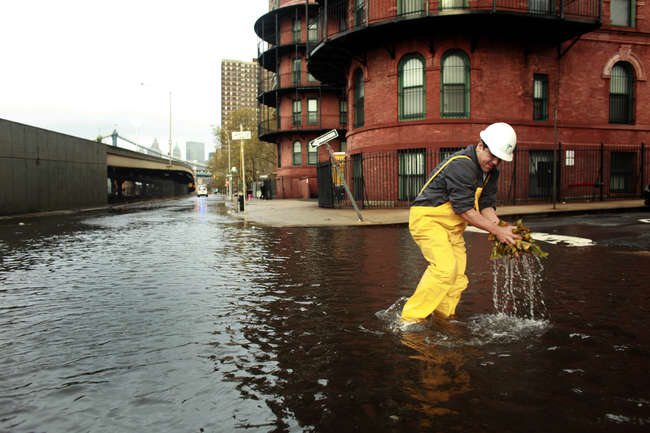 <p>A New York City worker clears a sewer drain in Lower Manhattan after Superstorm Sandy.</p>