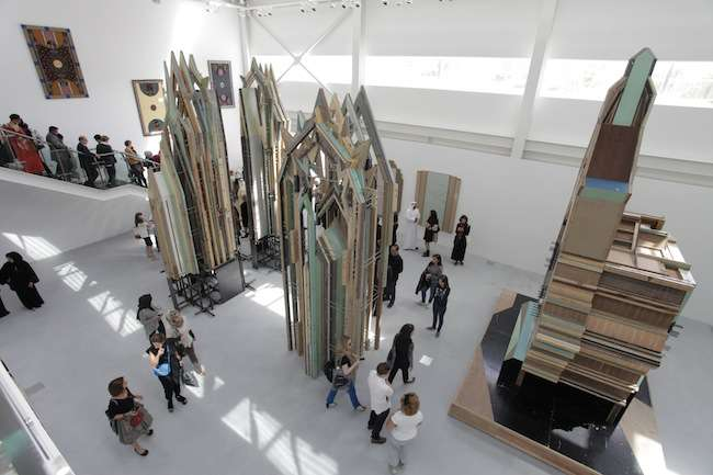 Cathedral-like sculptures made from salvaged doors by Liu Wei soar in the large, steel building's open space, the softness of its aging timber amplified by the indirect daylight.