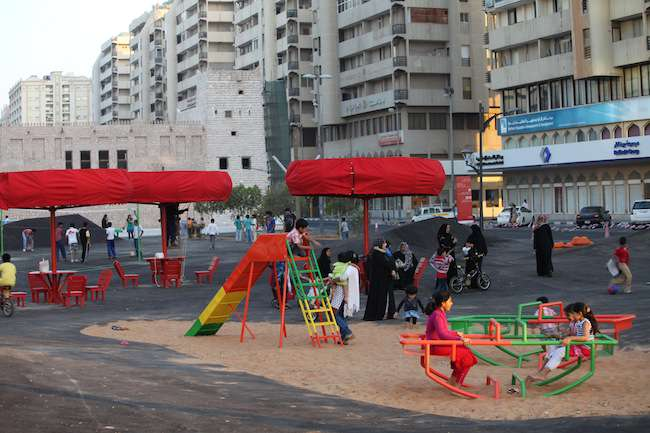 Unfortunately, Superflex placed its playground swings, benches, volleyball court, and other objects on a sea of asphalt running through the middle of a boulevard. The material retains daytime heat wel