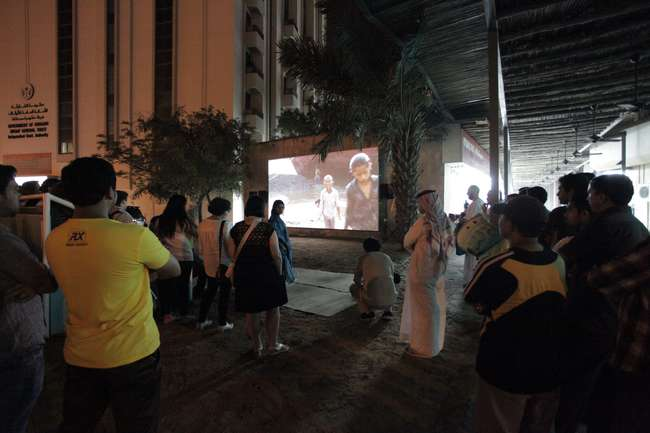 <p>Both foreign visitors and locals converge on an ad-hoc outdoor theater screening work by the Indian collective Camp. To make <em>From Gulf to Gulf to Gulf</em>, 2009-13, the artists gave cameras to
