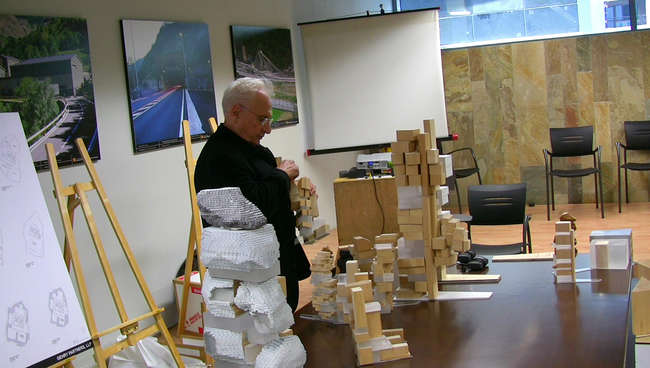 Still from <em>The Competition</em>: Frank Gehry looks over models before his presentation.