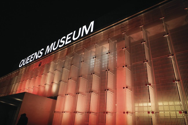 The west facade of the renovated Queens Museum features glass panels illuminated with programmable LED lighting.