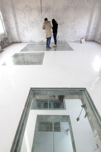 Inside the Silo Building, O-office Architects cut out rectangles in the floors and covered them with glass, creating remarkable views through the structure.
