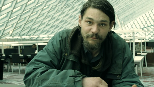 <p>Film Still from <em>REM</em>:</p><p>A homeless man takes refuge in OMA&#8217;s Seattle Public Library</p>