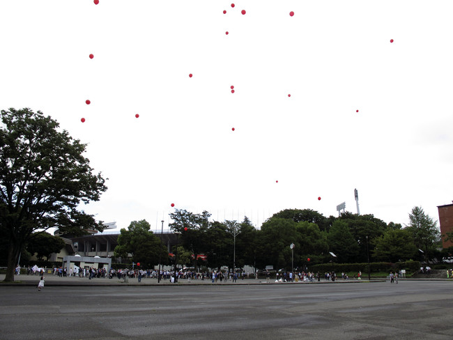 Protestors, including architect-activist Edward Suzuki (center), encircled the stadium carrying red balloons.<br /><div id='_mcePaste'>&#65279;&#65279;