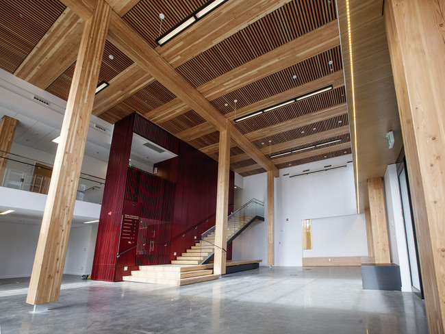 The timber post-and-beam structure is visible throughout the WIDC, including the double-story foyer.