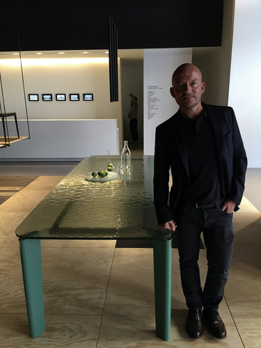 Designer Vincent van Duysen beside his new table for B&B Italia, inside the furniture company's showroom on Via Durini.