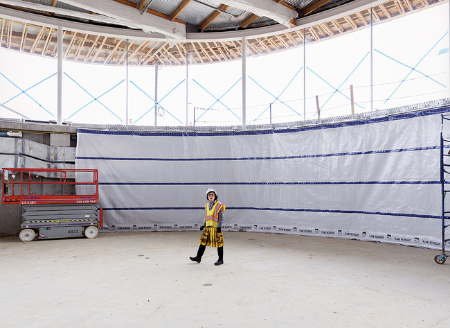 Kazuyo Sejima of SANAA inspects the construction progress inside the gymnasium in late March. The double-story space is sunk one level below grade in order to minimize its impact on the landscape.<div