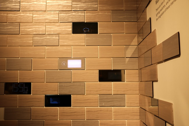 Conceptual wall tiles by Nissha transform with the touch of a finger from a marble stone or mirror finish to a digital interface where users can adjust temperature or access other home applications co