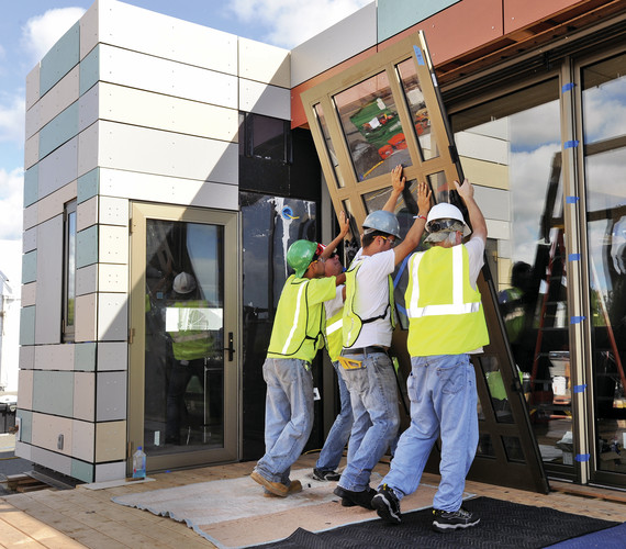 The combined team of Crowder College and Drury University install hurricane-resistant doors on their house.