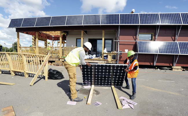Team members from the New York City College of Technology install solar panels on their house.