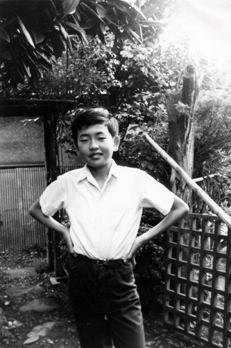 A young Kengo Kuma in front of his home.