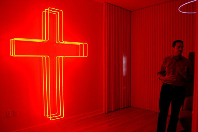 A neon cross illuminates a 'media room' inspired by <i>The Borgias</i>, a new show about an infamous Italian Renaissance family. Marc Thorpe, of Third Eye Studios, and David Schwarz, of Hush Studios,