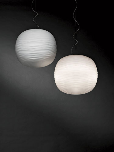 Designed by Ludovica + Roberto Palomba for Foscarini, this pendant gets its ethereal appearance from a white blown-glass sphere with a subtle bas relief of facets formed by crisscrossing grooves. The