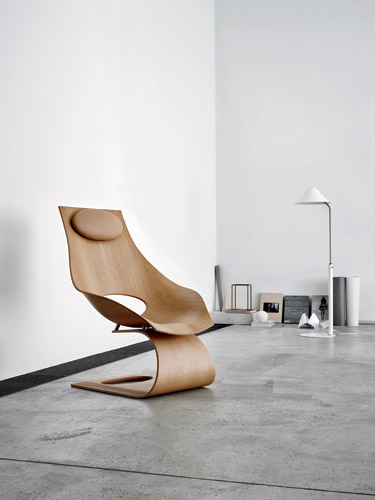 The chair is available in walnut or oak veneer, with a lacquer or oil finish.