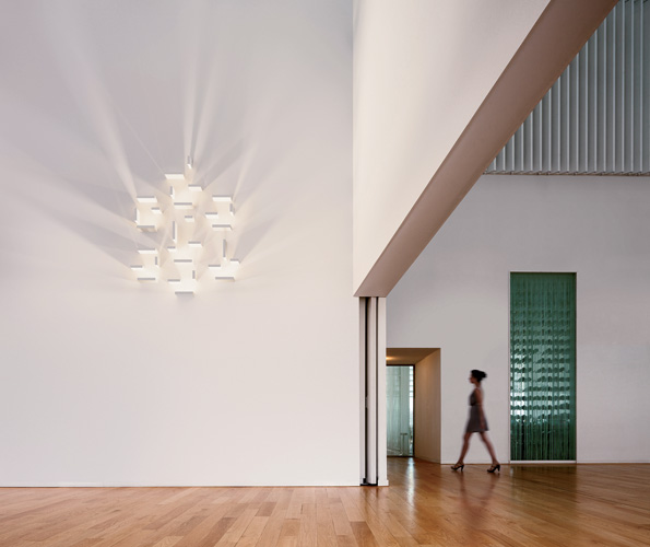 Playing with light and shadow, this wall fixture from Vibia comprises five blocks, only one of which holds the LED light source; the other four can be positioned to refract, reflect, and break up the