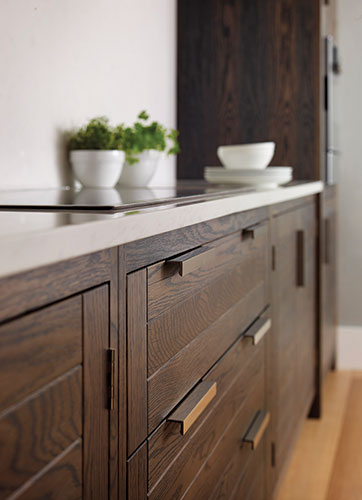 Handcrafted at the Humphrey Munson workshop in Felsted, England, the Markham kitchen features rectangular polished nickel handles, traditional joinery, and solid oak cupboard doors with a striking sla