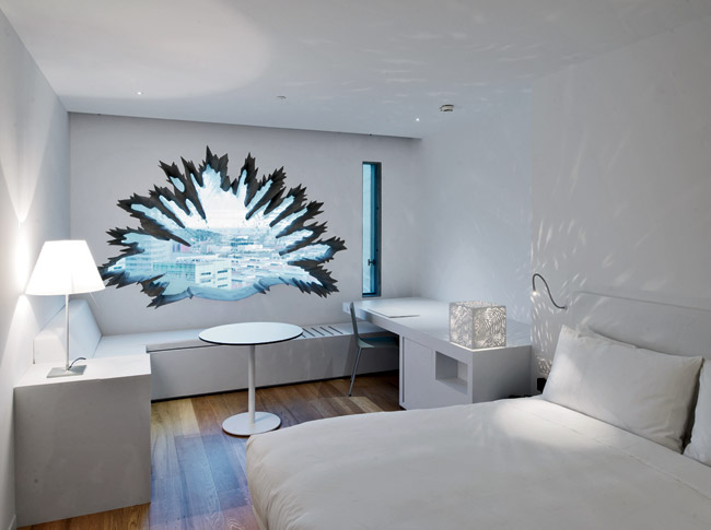 Palm-tree cutouts for guest-room windows. Nouvel designed furnishings throughout,including a cubic light fixture that projects changing patterns of palm fronds on the walls.