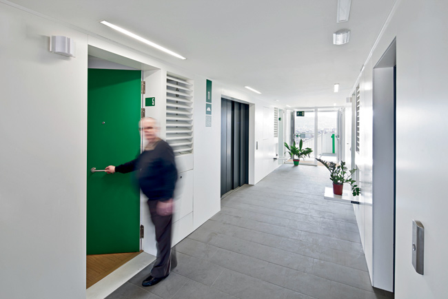 Corridors are extra-wide, with glazed ends opening to the outdoor stairs. The apartment units' louvered windows open to allow cross-ventilation.