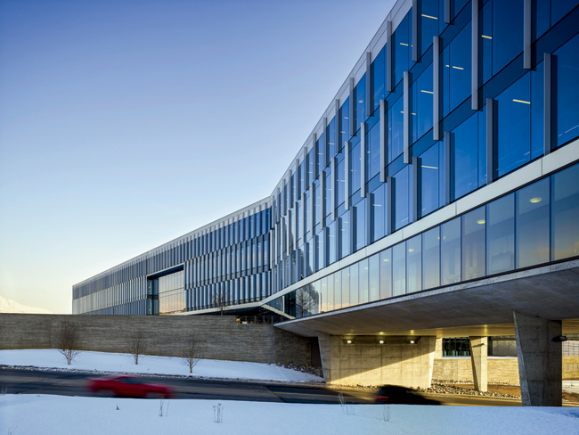 The new Adobe Systems Utah campus straddles a four-lane road, its board-formed concrete base stepping over the thoroughfare and its steel-and-glass shell rising overhead. Metal fins pr