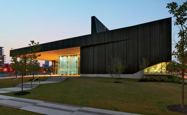 Glazed sections of the charcoal-zinc-paneled facade allow passersby glimpses into the Aquatic Centre. At night, the building becomes a lantern in the park, with light streaming from the transp