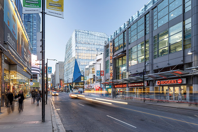 The building's distinctive form and the blue shard of the entrance canopy visually mark the gateway to Ryerson University amid the retail patchwork of the busy downtown street.