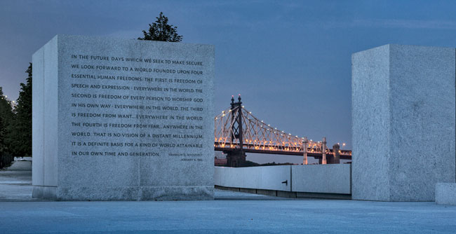 The Queensboro Bridge glows behind a granite block on which is engraved text from FDR's 'Four Freedoms' speech.