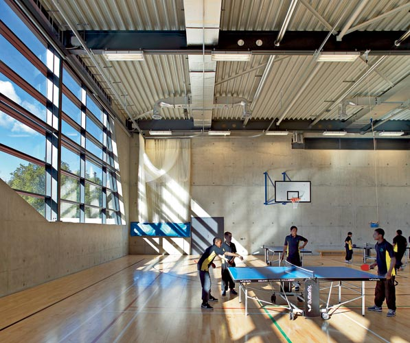 Large windows bring ample daylight into the school's industrial-style Sports Hall.