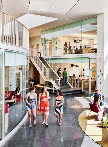 Open stairways in the double-height corridor, and floor-to-ceiling glass walls between classrooms and public spaces, create an airy yet intimate environment.