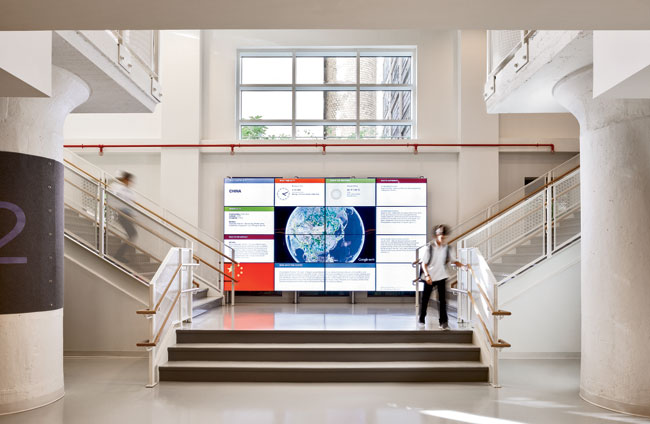 An interactive media wall dominates the grand stair that leads to the cafeteria and the High Line.