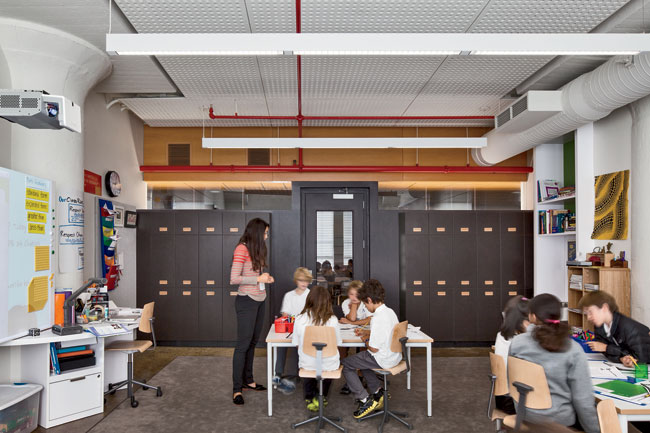 Clerestories, in-room lockers, and throw rugs over existing concrete floors make lower-school classrooms feel cozy, while distance-learning cameras and interactive boards provide the latest technologi